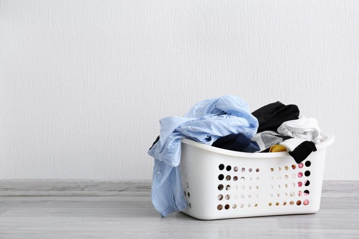 Basket with dirty laundry on floor against light wall