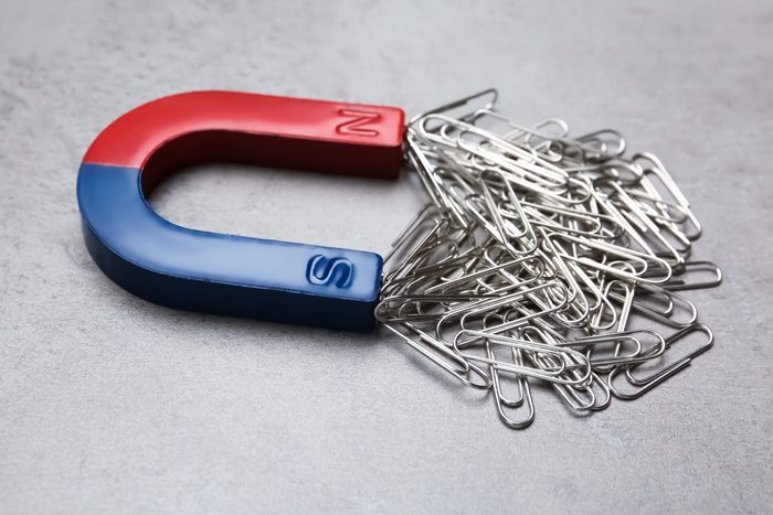 Magnet attracting paper clips on grey background
