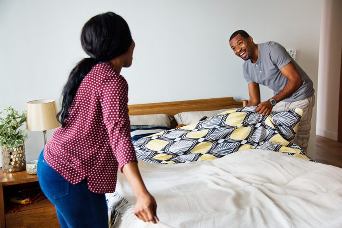 Black couple changing bed sheet together