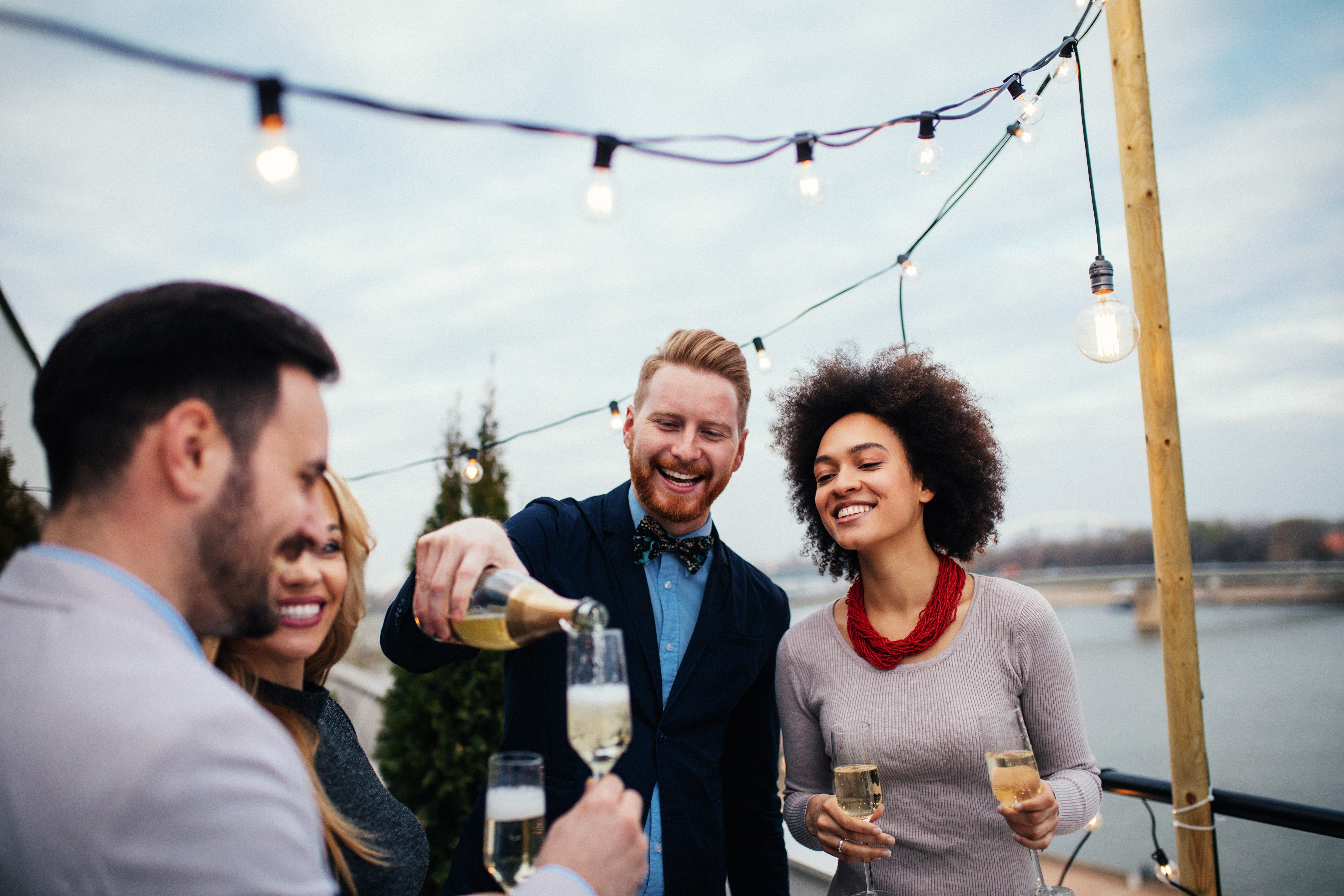 Friends celebrating on rooftop and drinking champagne