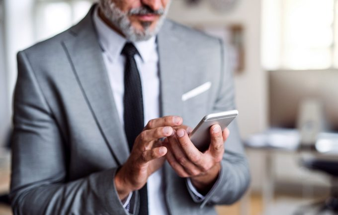 A midsection of businessman standing in an office, using smartphone.