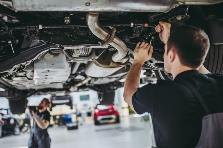 Two handsome mechanics in uniform are working in auto service with lifted vehicle. Car repair and maintenance.
