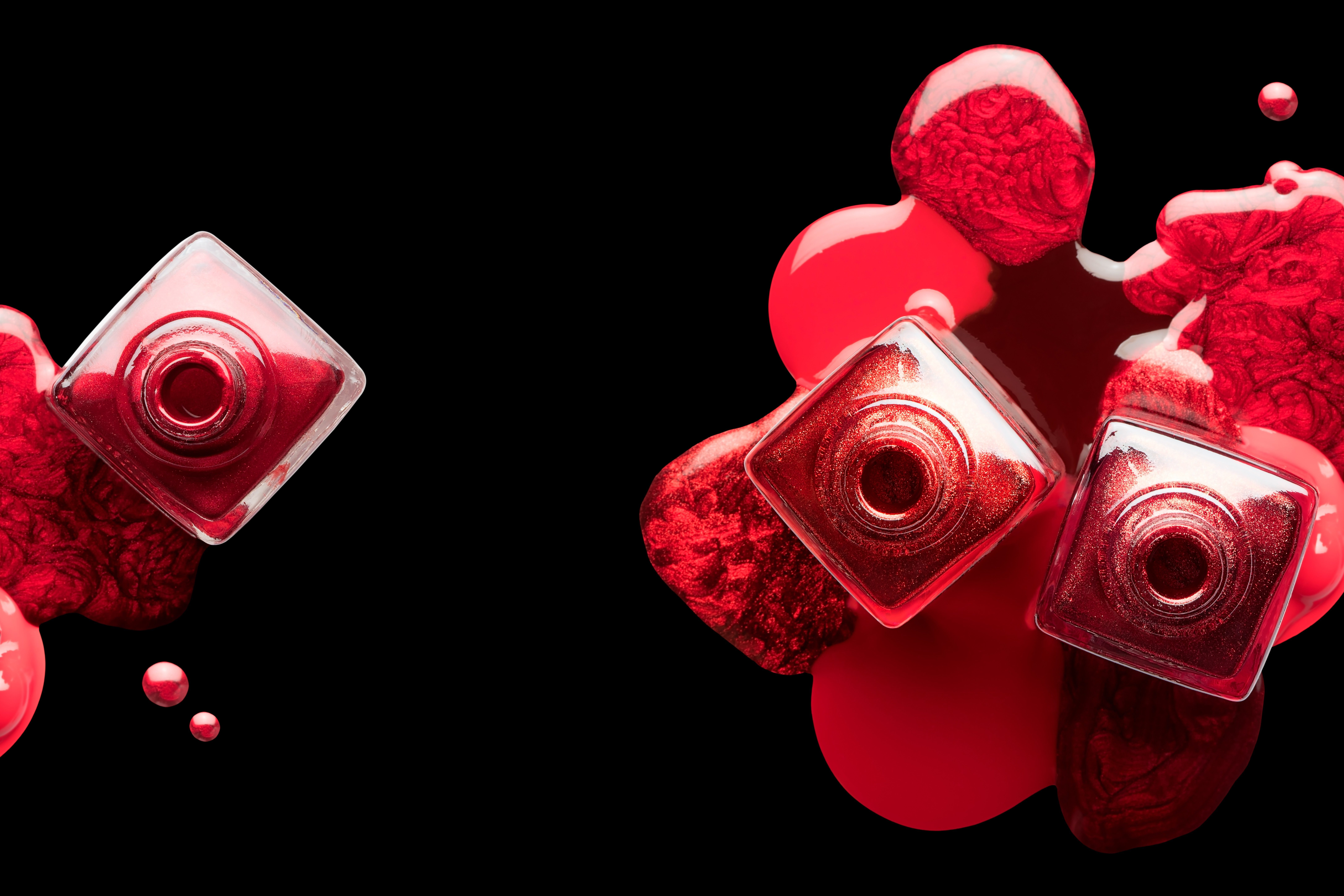 Nail art and manicure concept with metallic red lacquer or nail polish artfully spilled beneath three open bottles. Isolated on a black background, top view with copy space
