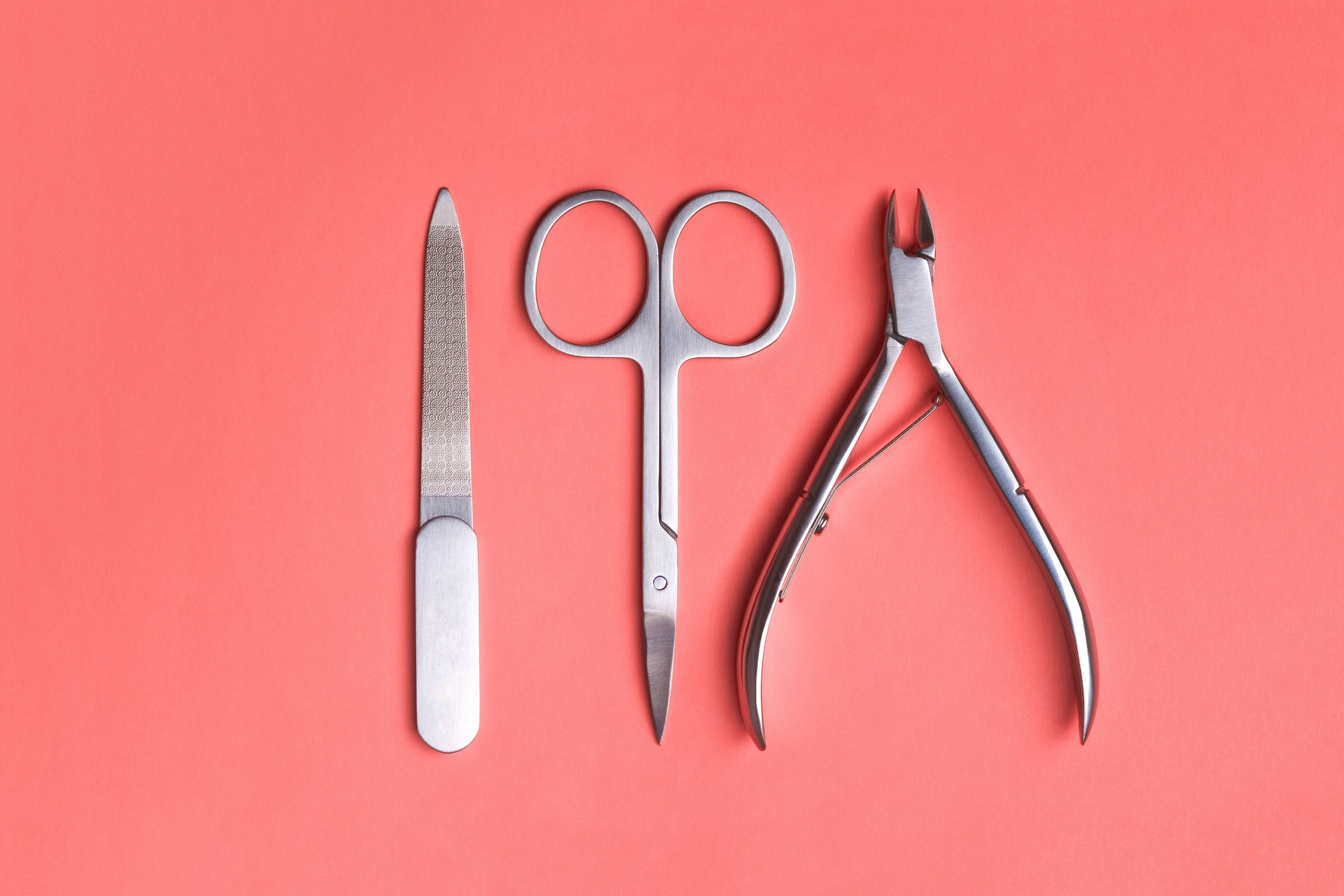 Various elegant manicure tools arranged on Living Coral background. Nail clipper, scissors and file. Color of the year 2019 concept.