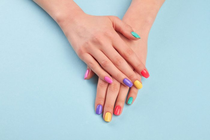 Female beautiful manicured hands. Woman hands with stylish colorful nails on light blue background. Skin and nail care.