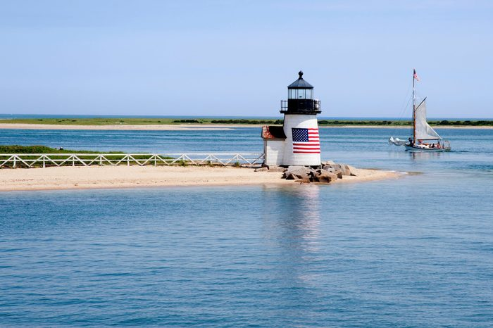 Sailing past Brant Point lighthouse on Nantucket Island on a warm quet summer day in New England.
