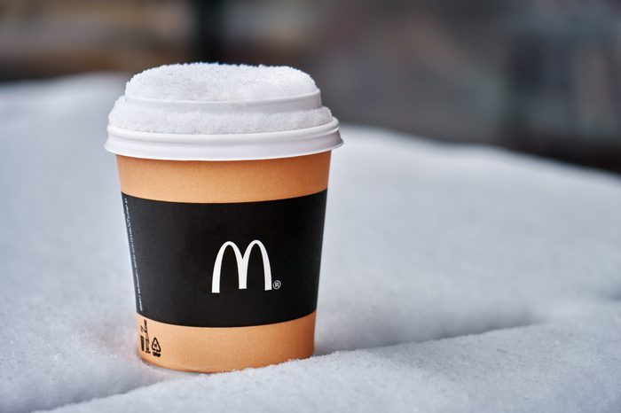 Obninsk, Russia - January 4,2019. Mcdonald's paper cup of coffee standing on the table covered with snow outdoors in winter