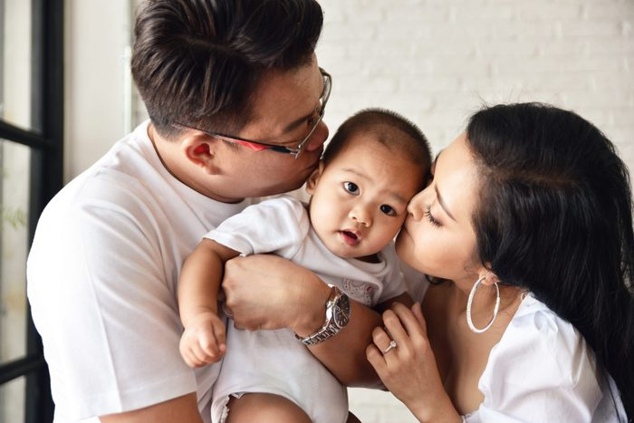 Asian woman and man kissing their baby with love.Mother and Father with lovely son.Happy family concept in house.Love and relationship idea.Warmness and happiness.Parent with little boy.