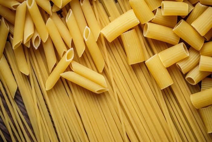 close up portrait of raw homemade italian pasta, macaroni, spaghetti, and fettuccine
