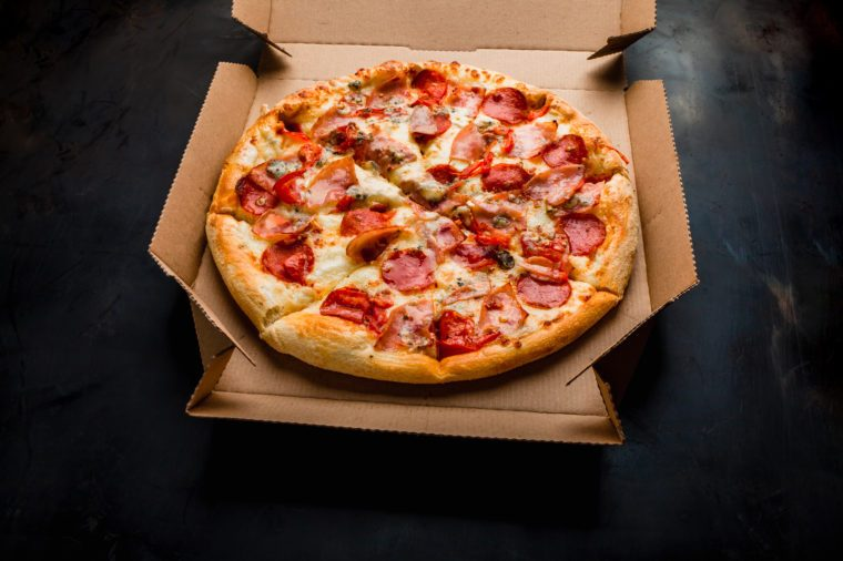 Pizza in a cardboard box against a dark background. Close-up. View from above. Pizza delivery. Pizza menu.