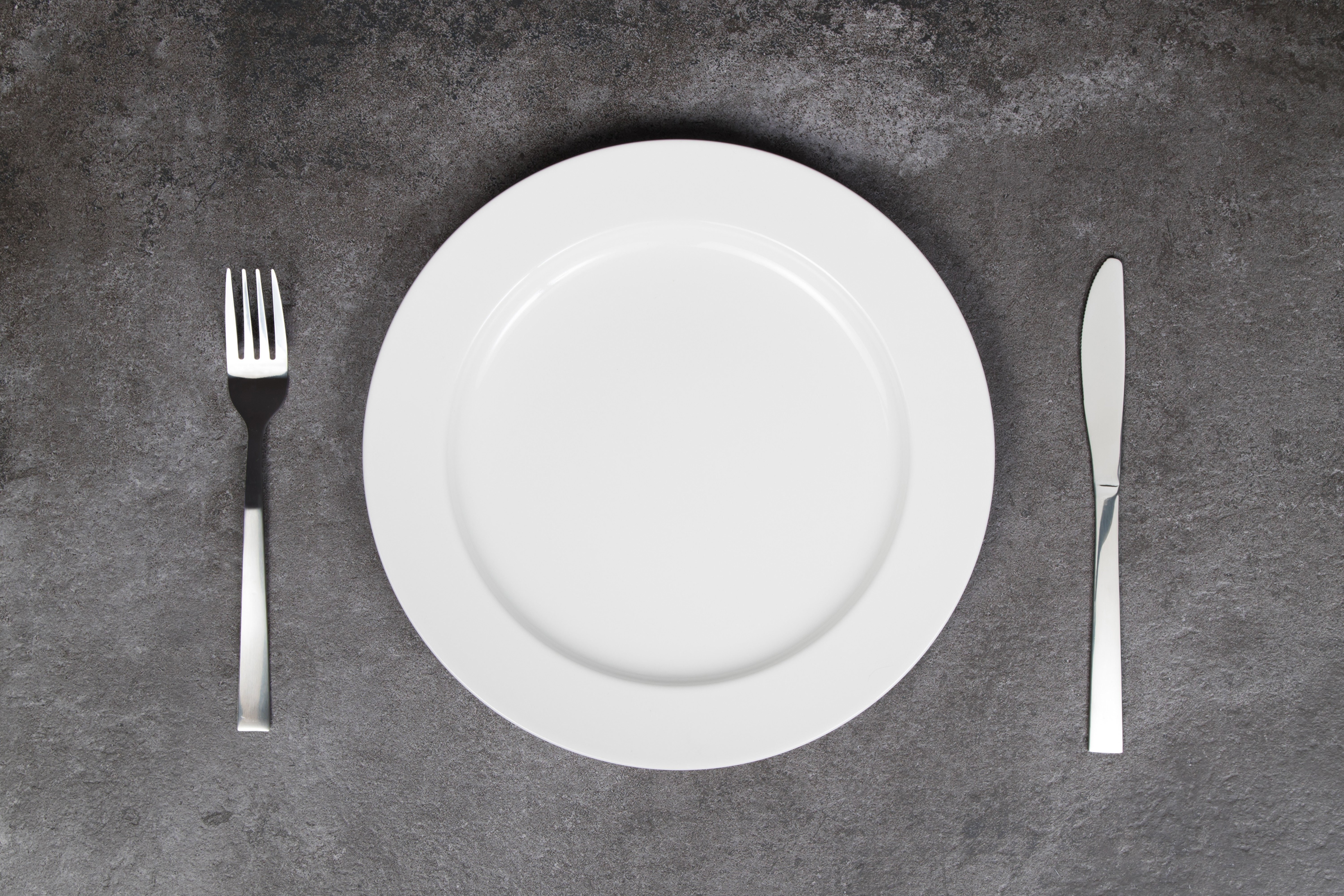 White empty plate with fork and knife on grey background