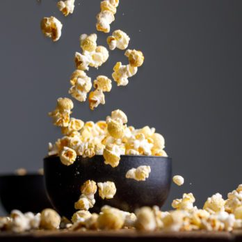 Levitating popcorn around a ceramic bowl. Appetizing still life.