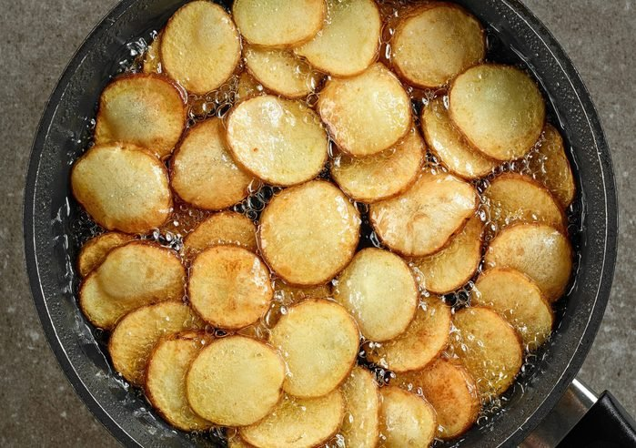 frying potatoes in pan with oil, top view