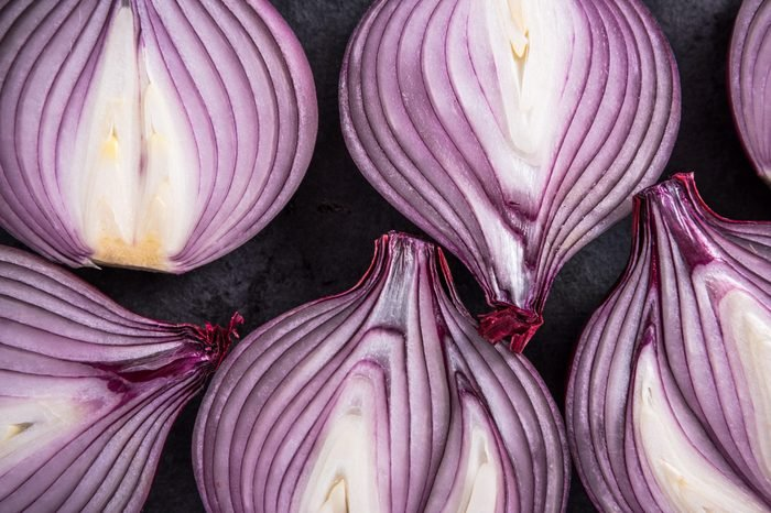 Red onion halves, texture details and pattern, flat lay from above