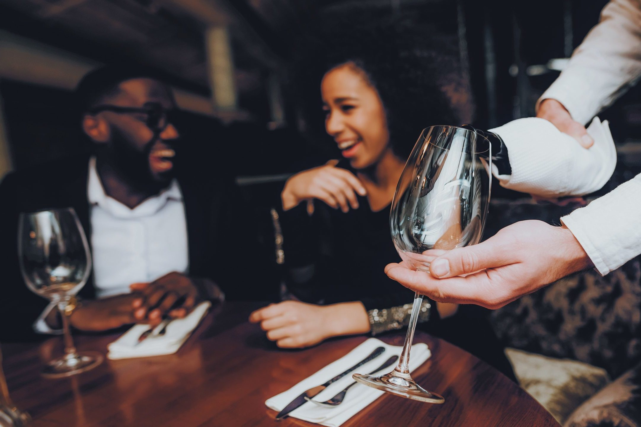 Waiter Pouring Wine to Glass Couple in Restaurant. Romantic African American Couple in Love Dating. Cheerful Man and Woman Drinking Red Wine. Romantic Concept. Anniversary. Bottle of Red Wine.