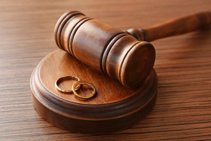 Golden wedding rings with judge gavel, closeup