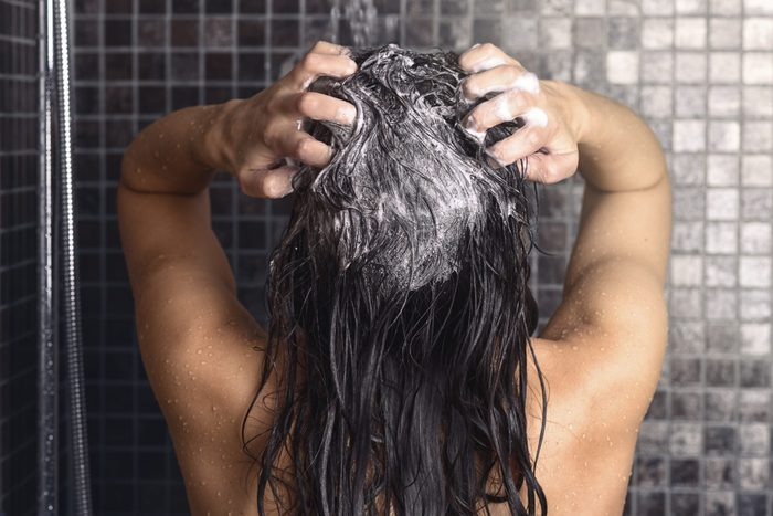 Woman shampooing her long brown hair under a shower standing with her back to the camera working up a lather under the spray of water