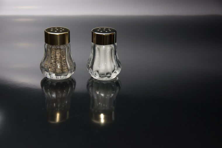 Salt and pepper shakers on black background.