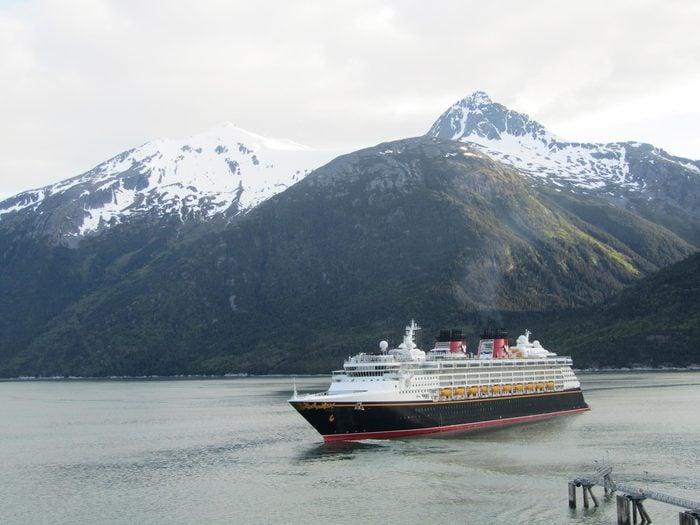 Juneau, Alaska, USA on 05.06.2018: Disney Wonder in front of the fantastic Alaskan scenery