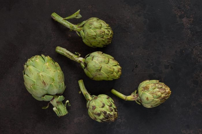 Close up photo of fresh artichoke. Top view on dark background.
