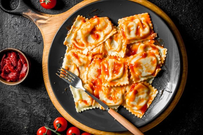 Ravioli with veal and tomato sauce. On black rustic background