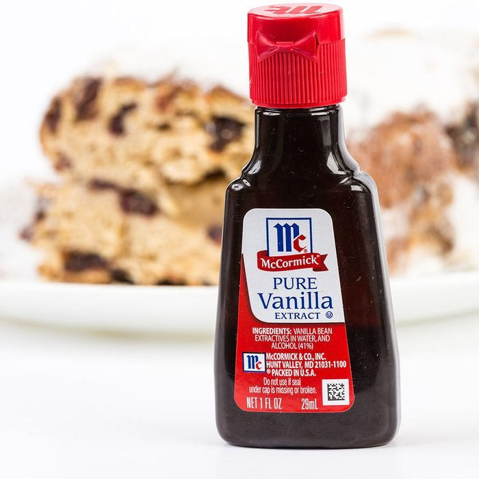 LLANO, TEXAS-DEC 24, 2014: Small bottle of McCormick Pure Vanilla Extract with baked cake in background. Horizontal with copy space.; Shutterstock ID 239758756