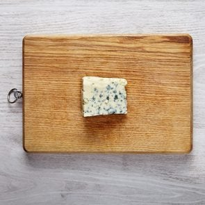 One piece of fresh roquefort cheese on wooden board