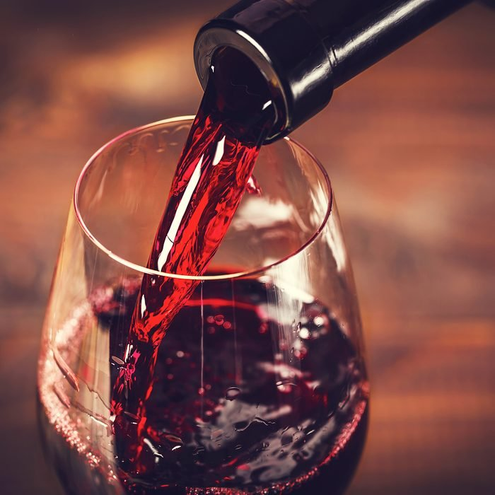 Pouring red wine into the glass against wooden background; Shutterstock ID 370977980
