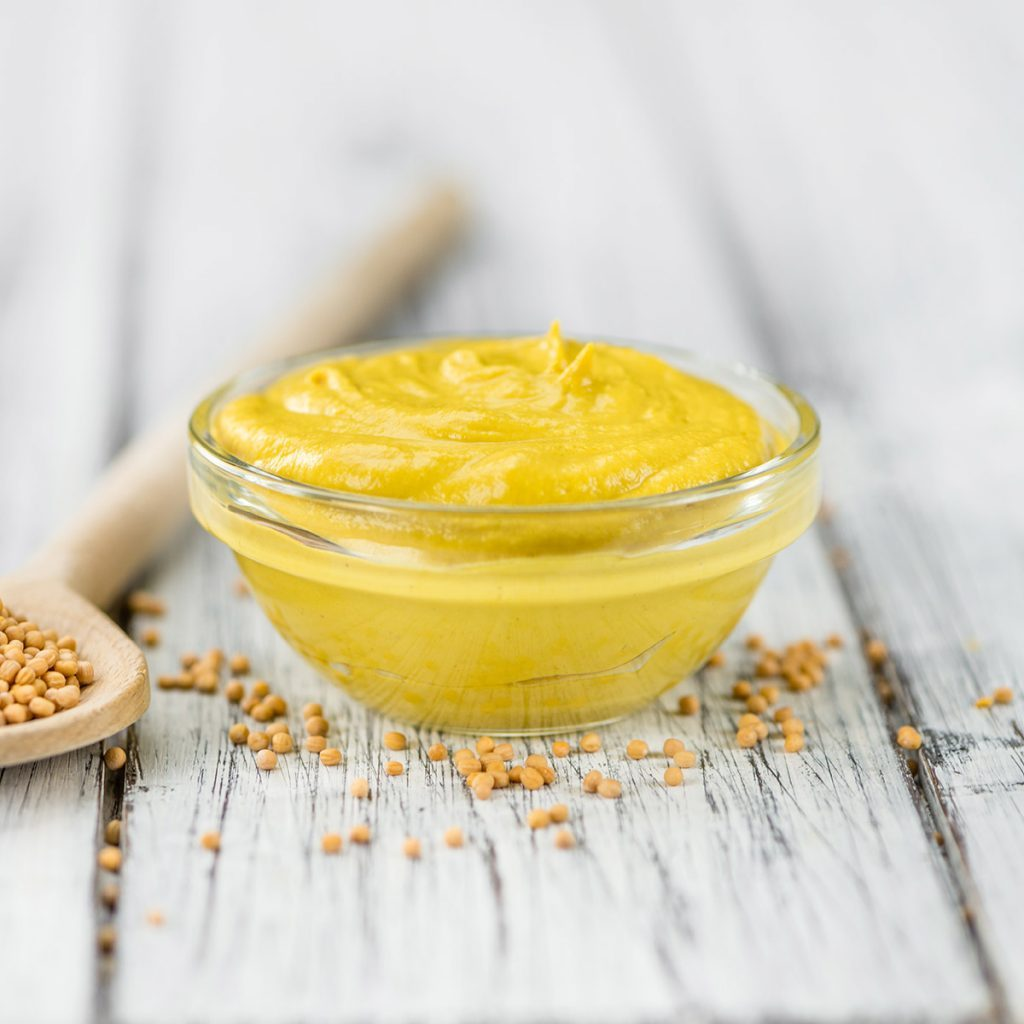 Fresh made Mustard on a vintage background (close-up shot); Shutterstock ID 562035217
