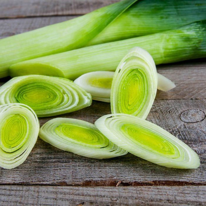 Fresh leeks whole and sliced on a wooden kitchen board; Shutterstock ID 583263889