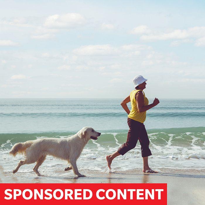 Happy elderly woman running along a beach with her golden retriever