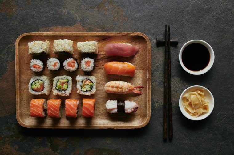 top view of assorted sushi set on wooden plate, chopsticks, ginger and soya sauce in bowls on dark tabletop