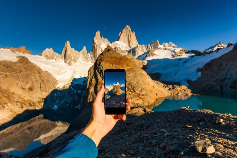 Taking a photo of mountains on a smartphone. Patagonia.