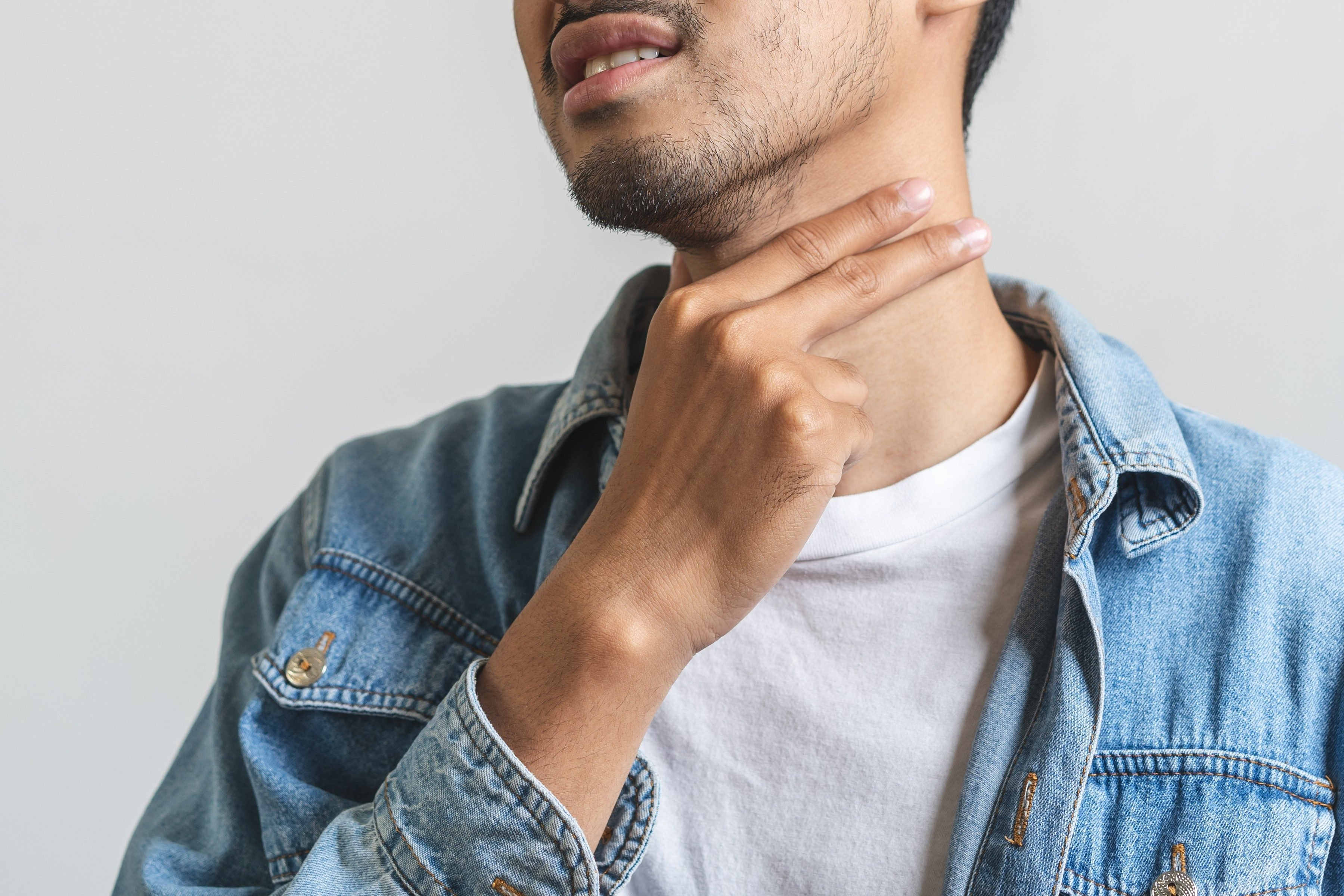 Close up asian man touching his neck and having sore throat.
