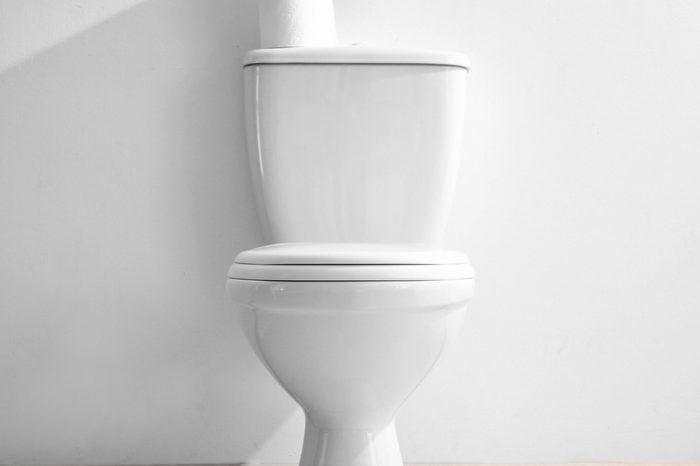 New ceramic toilet bowl near light wall