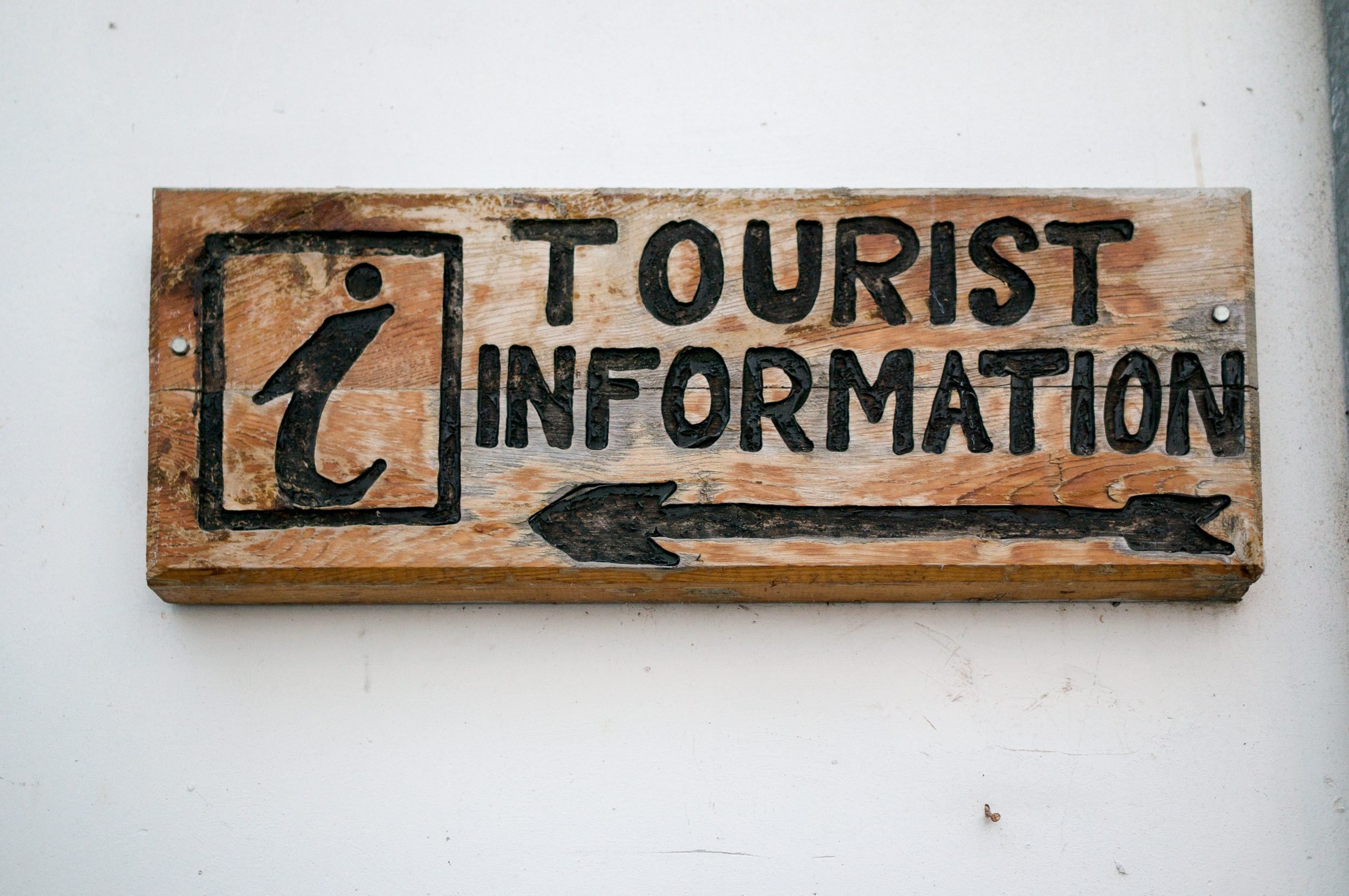 Wooden Sign of Tourist information On A Wall