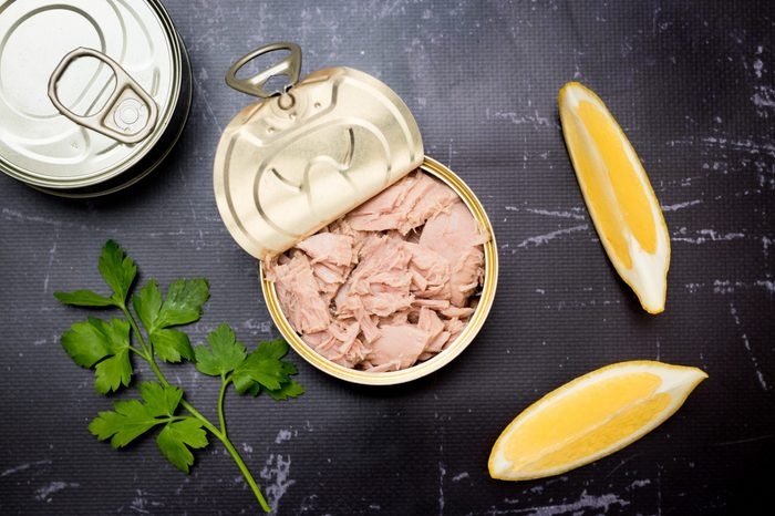 Opened tuna can with parsley and lemon slices on a black cutting board.