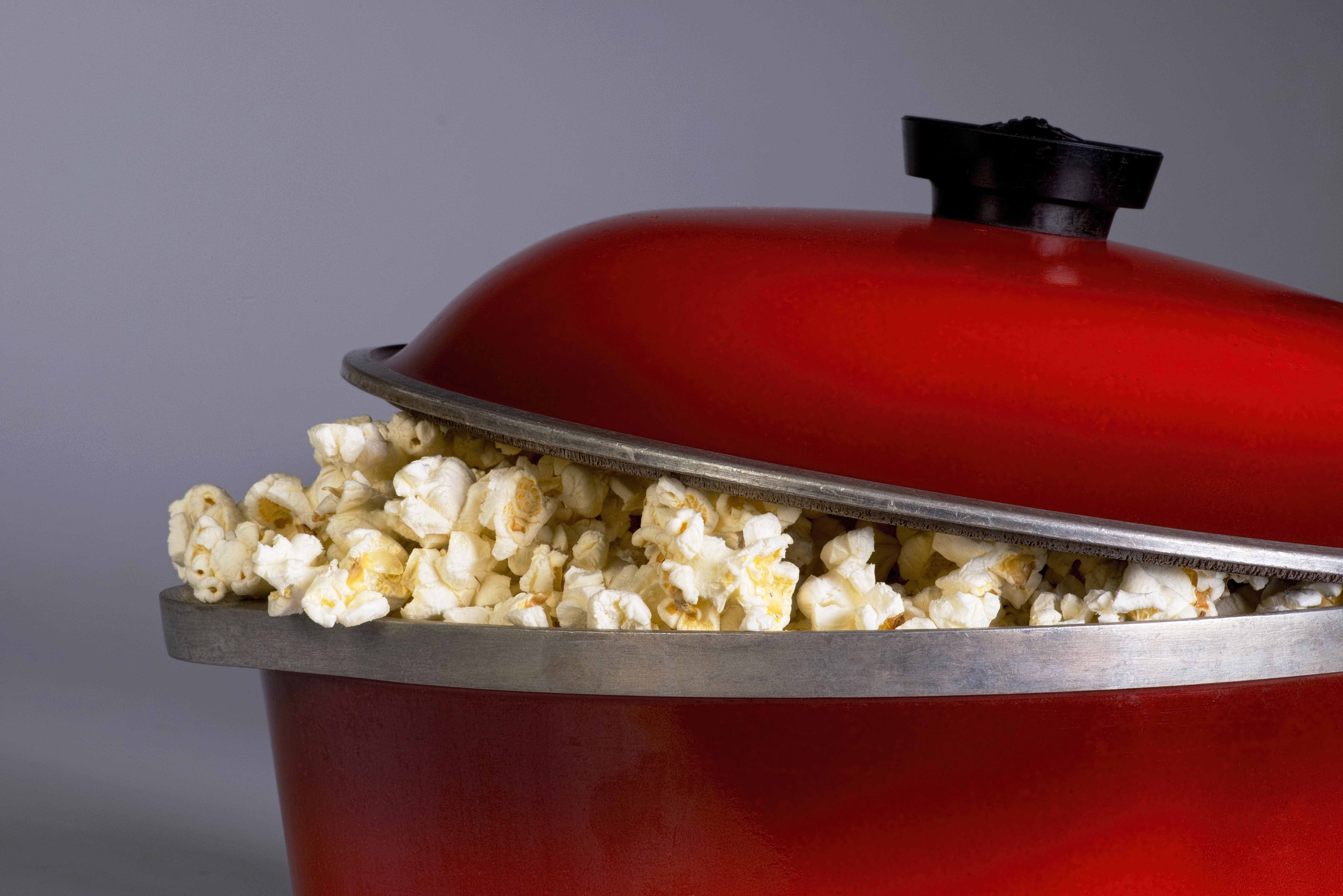 Popping popcorn the old fashion way in a red iron pot.