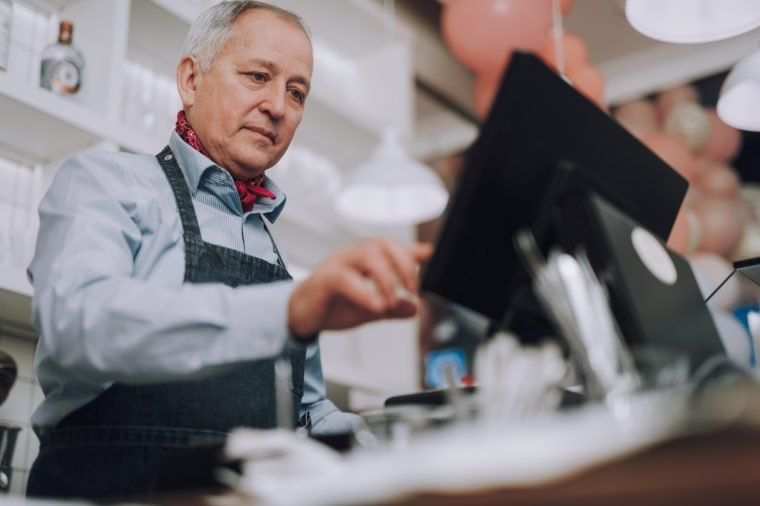 Low angle portrait of good-looking gentleman operating at the cash desk in cafe and checking orders on monitor