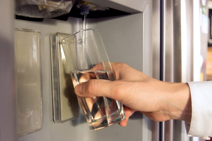 Male hand is pouring cold water from dispenser of home fridge.