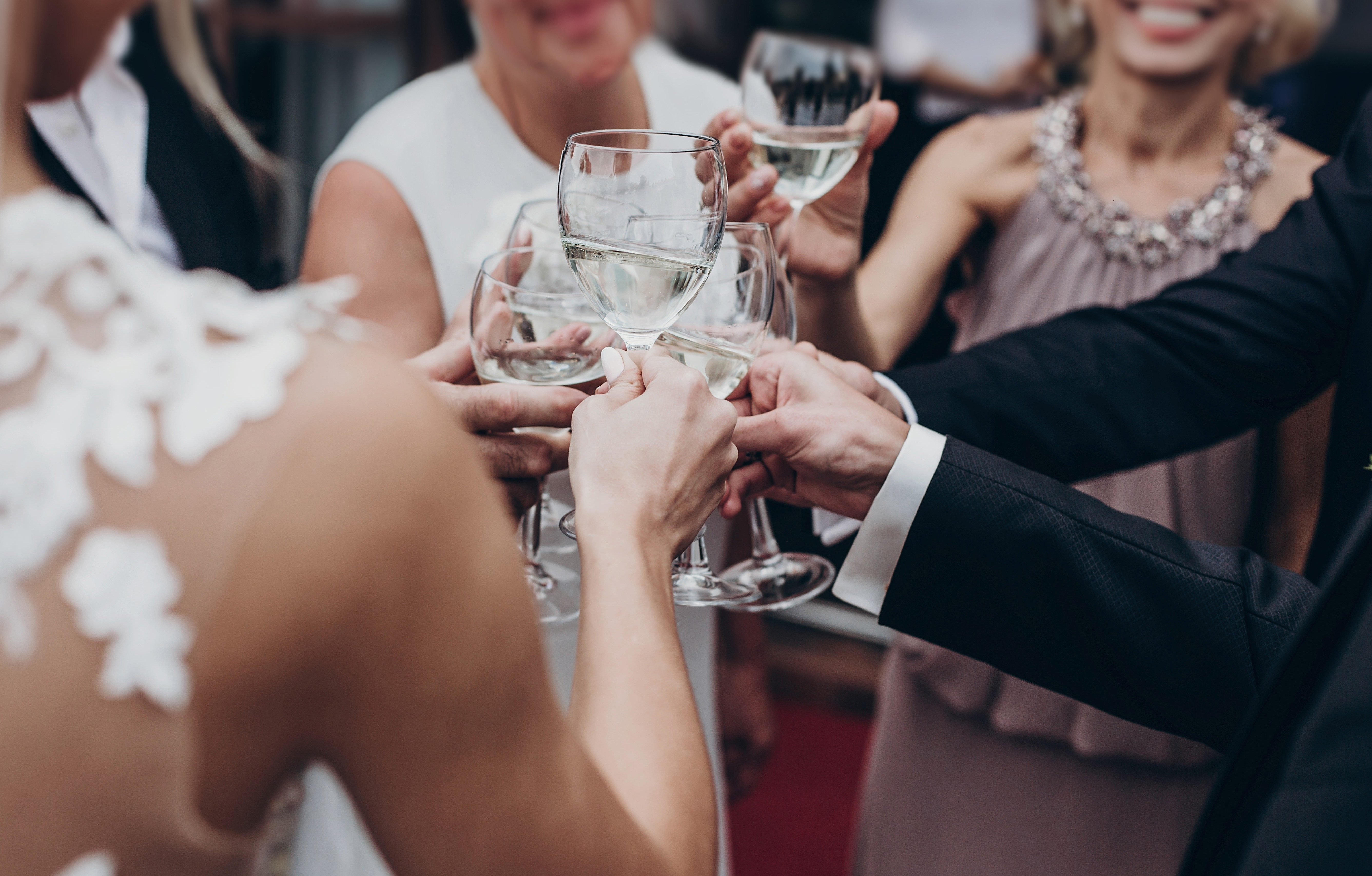 christmas luxury celebration feast. champagne and wine glasses in hands at luxury wedding reception at restaurant. guests toasting and cheering at stylish celebration. space for text