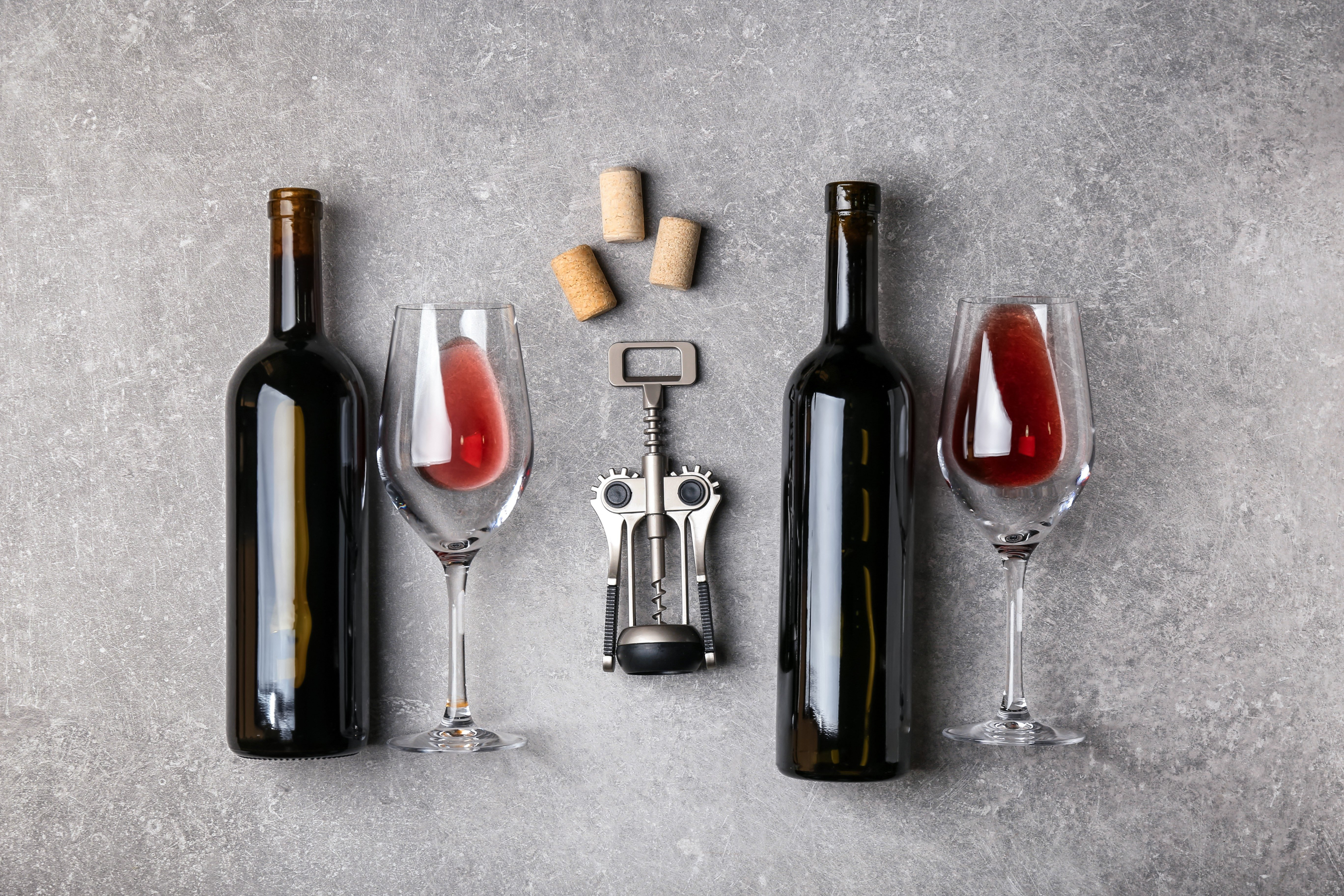 Composition with bottles of red wine and glasses on grey background