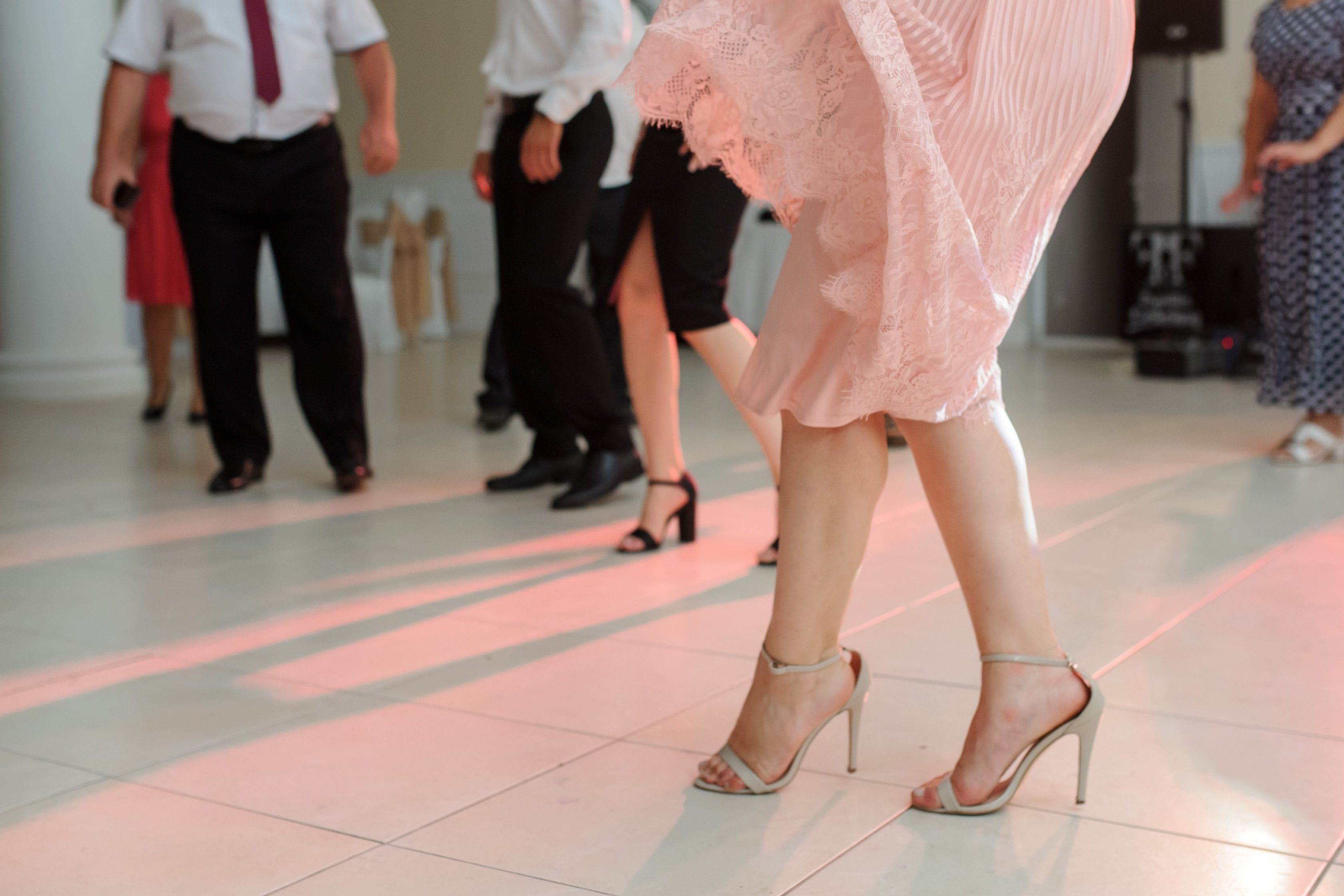 close up photo of woman legs in stylish high hell shoes on floor dancing at a wedding party