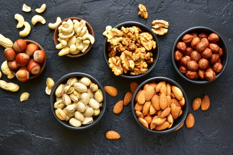 Assortment of nuts on a black slate or stone background - healthy snack.Top view .