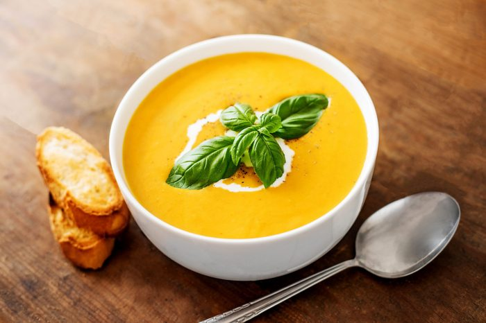 Bowl of squash soup with basil leaf on wood table. Pumpkin soup served in a bowl, top view
