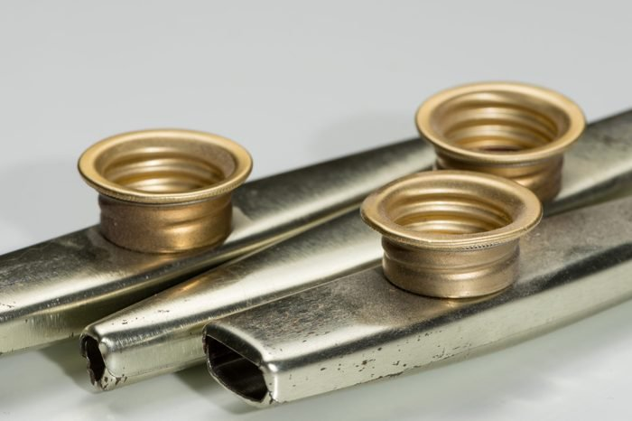 Closeup of metal kazoos on a white reflective surface