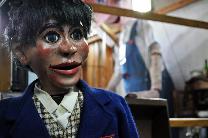 Creepy old puppet dummie of a boy in school suit