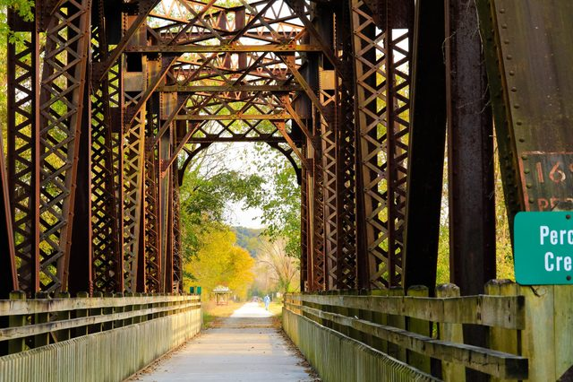 Fall view of a former railroad bridge converted into a trail in Missouri State Park in the fall; fall trees in the background