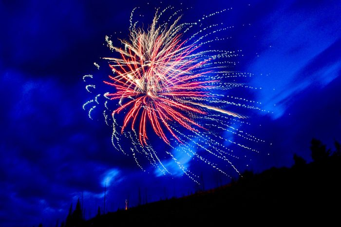 Fireworks explode over the mountains near the entrance to Yellowstone National Park (Cooke City / Silver Gate), Montana.