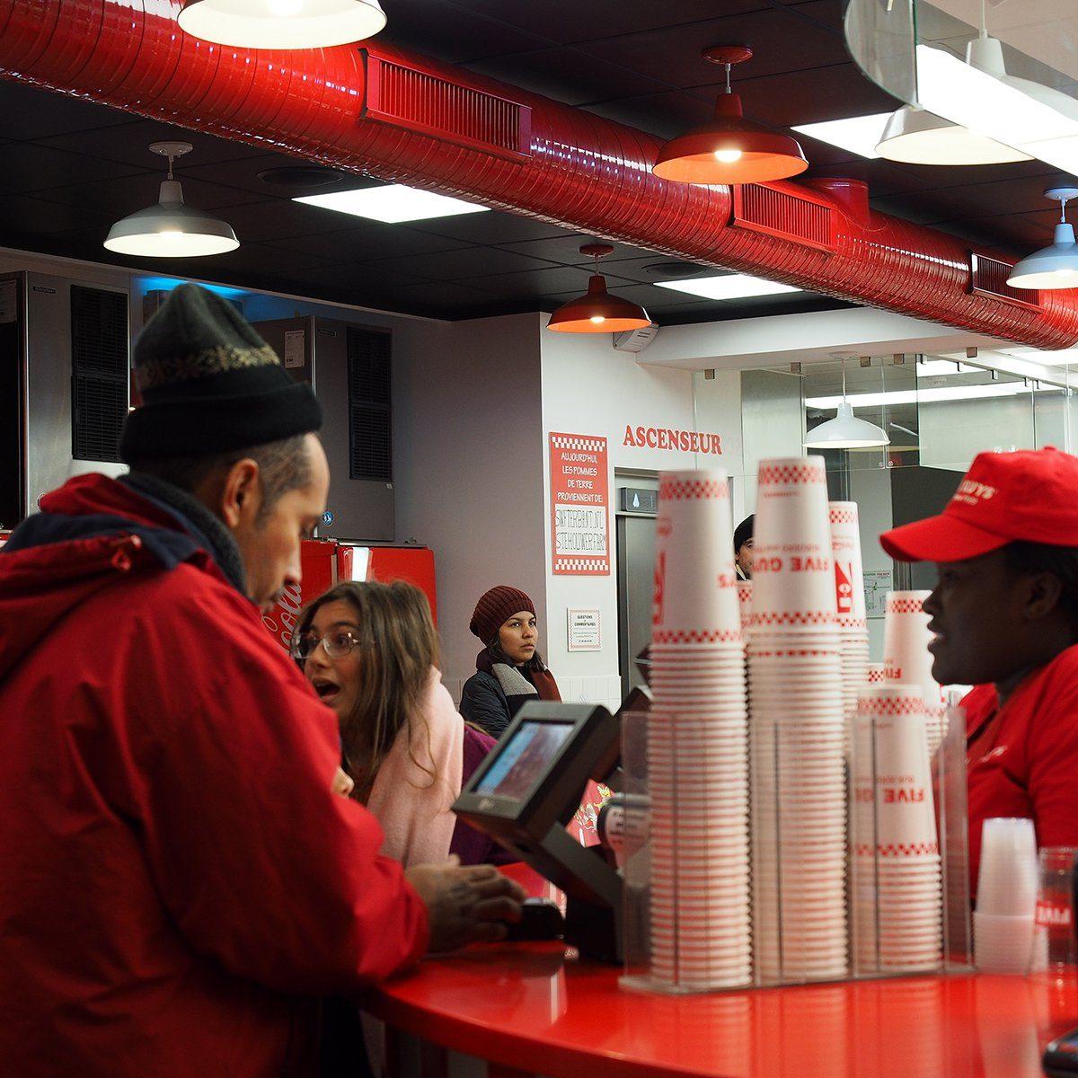 Closeup of crews working at Five Guys burger chain busily, Avenue des Champs-Élysées, Paris, France